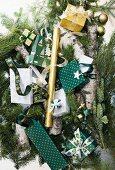 Kleine Geschenktüten und Päckchen mit Weihnachtsmotiven auf Tannenzweigen und Baumstämmen
