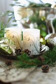 Verzierte Kerzen und kleine Tannenzapfen auf Schale in weihnachtlicher Stimmung