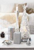 Stillleben aus verschiedenen Kerzenformen in Silber auf weisser Ablage