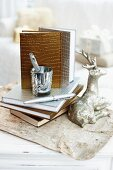 Notizbücher mit gold- und silberfarbenem Kroko Einband neben silberner Rentierfigur und Schreibutensilien auf Vintage Papier