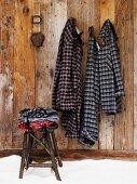 Kleidung auf rustikalem Hocker vor Holzwand mit aufgehängten Pyjamas im Karolook an Wandhaken