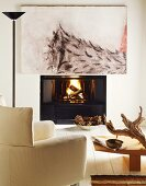 Modern painting above burning fire in open fireplace; comfortable white reading chair in foreground