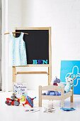 Doll's bed, toys and easel in child's bedroom