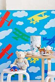 Child's chair and table with toys, child's crockery and money box against wallpaper with aeroplane motif