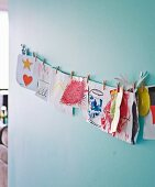 Collection of colourful painted pictures pegged on cord on pastel turquoise wall