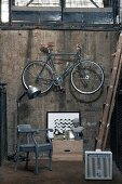 Armchair, retro lamp, picture and bust of a woman below bicycle hanging on cellar wall