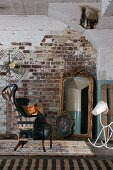 Battered wingback chair, mirror, painting of the Madonna and stylised rocking horse against old brick wall