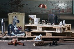 Bizarre objects and decorative items on stacked euro pallets against old brick wall