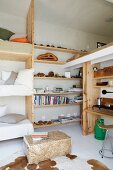 Space-saving bunk beds next to DIY wooden shelving on wall with cowhide rug in foreground