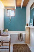 Simple bathroom with bathtub against light blue wall and small window; towels on chair and sisal runner in foreground