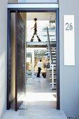 Blick durch die geöffnete Haustür auf Galerietreppe