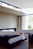 Dunkles Bettgestell in minimalistischem Schlafzimmer