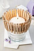Glass tealight holder decorated with clothed pegs
