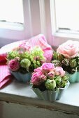 Small flower arrangements with pink roses in china flan dishes from the fifties