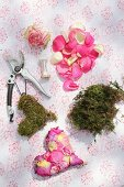 Materials for crafting decorative heart from moss, yarn and rose petals of various colours
