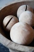 Hand-crafted wooden balls in old wooden bowl