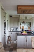 Bright, Shaker-style, country-house kitchen with sink unit and old wooden stools on marble floor tiles in natural shades
