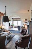 Samtgepolsterte Sessel und Landhaustisch als Sitzgruppe vor Kamin; Blick durch Rundbogen auf angrenzenden Fernsehraum