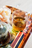 Glass teapot, tea glass and sweets on printed tray