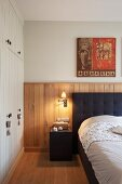 Double bed with charcoal upholstered headboard against oak wood panelling and white fitted wardrobe to one side