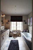 Shaker-style bathroom with pale wood-panelling, dark surfaces and marble floor tiles in natural shades