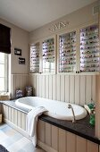 Collection of multicoloured tiny bottles in lit glass-fronted cabinets above fitted bathtub with wood-clad side and stone surround
