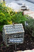Brick-edged herb bed decorated with plant tags and ornate cloche