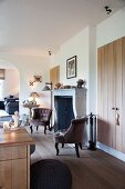 Antique-style armchair in front of open fireplace and fitted cupboards with simple board doors in open-plan interior
