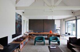 Grosszügiges Wohnzimmer mit raumhaltigem Dach und niedrigen, umlaufenden Holzeinbauten mit integrierter Schreibtischplatte