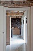 Blick in die Küche entlang einer Gangflucht mit sichtbaren alten Holzbalken in renoviertem Haus