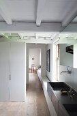 Blick vom Bad mit dunkelgrauem Doppelwaschtisch in eine Gangflucht