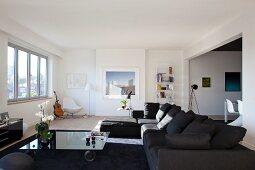 Moderne, graue Sofakombination und rollbarer Couchtisch mit Glasplatte in grossräumigem, modernem Wohnzimmer