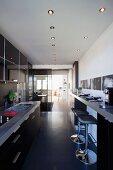 Offener Küchenbereich mit Barhockern an Frühstückstheke gegenüber Einbauküchenzeile und Blick ins Wohnzimmer