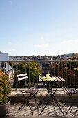 Klapptischgarnitur auf sonnigem Balkon mit Blick über die Dächer von Brüssel