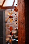 Aufgefädelte Herbstblätter und Nüsse neben Holzpfosten im Hausflur
