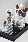Kleine Acrylglasboxen zur Aufbewahrung von Schmuck und Brillen auf schwarzem Tablett