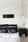 Schlafzimmer mit japanischen Dekokissen und Pendelleuchte an flexibler Roll-Aufhängung