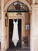 Still life with nostalgic wedding dress on a wooden door in a paneled room