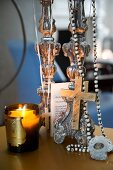 Lit candle lantern next to necklace with cross pendant