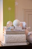 White, decorative, spherical candles with stars on stacked books in front of bright green stripe on wall