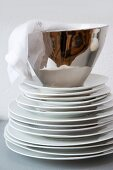 Linen napkin in silver china bowl on stack of white plates against white wall