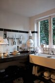 Modern kitchen with black stone worksurface and trough-style sink with vintage tap fittings below window