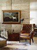 Antique leather armchair in front of wooden partition and picture of horses