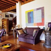 Purple sofa below modern artwork on wall in open-plan interior with wood-beamed ceiling