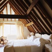 Attic bedroom with exposed, rustic wooden roof structure