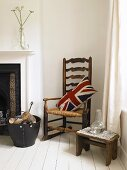 Union Jack pillow on an old rocking chair, wooden stool and basket with firewood by a fireplace