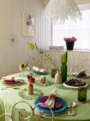 Gedeckter Tisch mit grüner Tischdecke in einem Esszimmer mit weisser Holzverkleidung