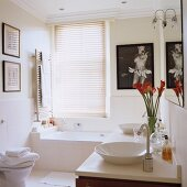 Vase of flowers on modern washstand and artworks on walls in bright bathroom