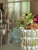 Garden flowers in narrow cylindrical vases next to a kitchen sink in a stainless steel countertop with mirror effect