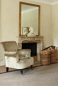 Antique reading armchair covered in gray velvet and wicker basket and firewood in front of an open fireplace with a traditional feel. Large wall mirror on the mantelpiece with a bust in front of it